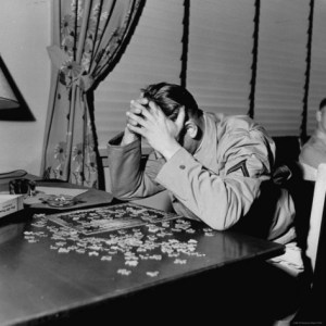man putting puzzle together