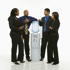 business group standing around water cooler.